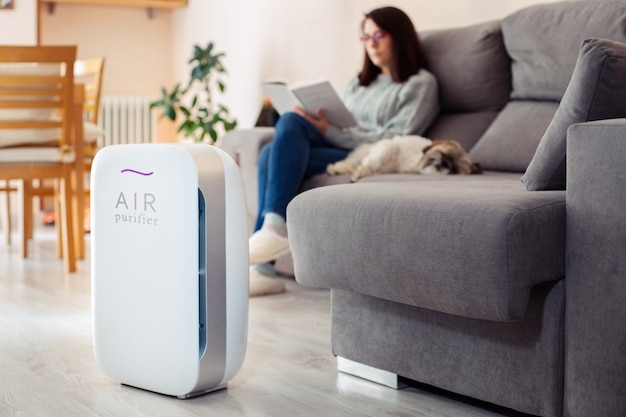Woman at home reading on the sofa with her pet in a clean and safe environment from virus by air purifying filter.