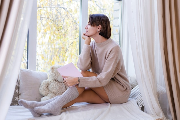 La donna a casa con il taccuino si siede sul davanzale della finestra in un maglione comodo e calzini di lana calda, fuori dalla finestra fredda fuori dalla finestra