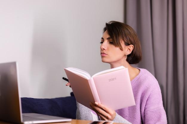 Donna a casa con il taccuino del blocco note pensando ai piani