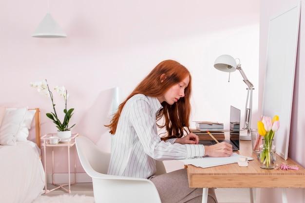 Donna a casa che lavora al computer portatile