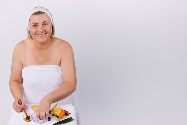 A woman at home, wrapped in a white towel with a smile, prepares a face and body mask from natural products. white background and empty side space. high quality photo