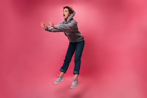 La donna in felpa con cappuccio e jeans sembra sorpresa e salta su sfondo isolato. ragazza scioccata emotiva in pantaloni denim si muove su sfondo rosa