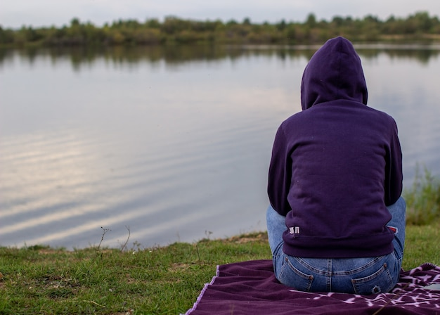 Woman in a hoodie sits and looks at the lake and looks into the distance. autumn cool evening on the lake. rear view.