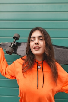 Woman in hoodie stands with a longboard in her hands