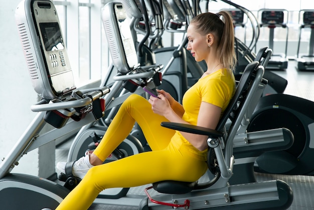 Woman on horizontal exercise bike in gym