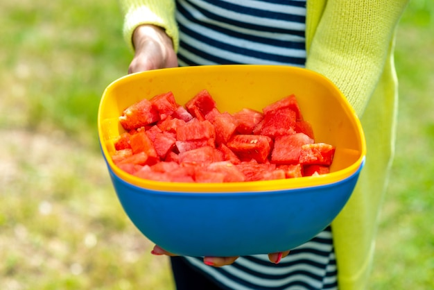 A woman on a hot day offers sliced pieces of watermelon.