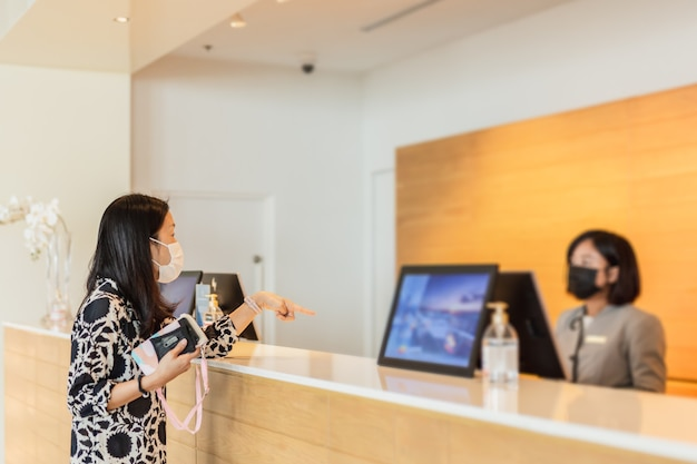 Woman hotel guest and receptionist at hotel counter wearing medical mask against virus.