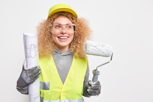 Woman house painter holds paint roller and blueprint busy making repairing dressed in working clothes wears protective glasses helmet gloves