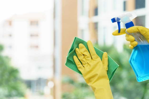 Woman housekeeper cleaning the mirror with green cloth