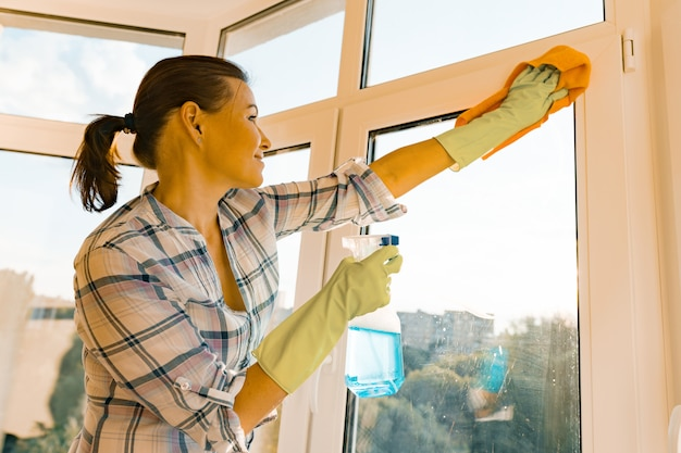 Woman housekeeper cleaning windows
