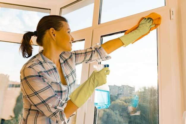 Woman housekeeper cleaning windows