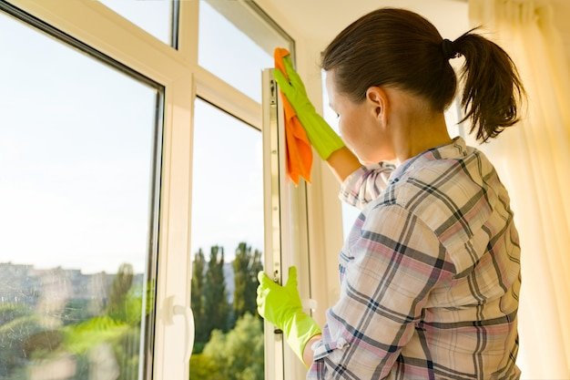 Woman housekeeper cleaning windows.