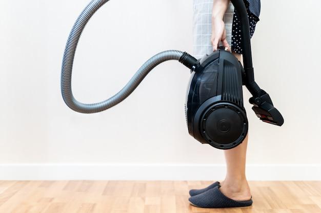 Woman housekeerer carrying an electric modern vaacum close up.