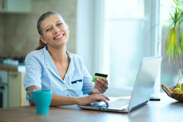 부엌에서 집에 있는 여성 주부는 노트북이 있는 테이블에 앉아 있습니다. 의사 소통, 휴식, 가정 및 온라인 쇼핑에서 작동