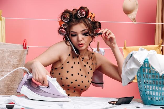 女性、主婦がまな板にアイロンをかけ、同時に化粧をしている。ピンクの背景に服を着てロープ。