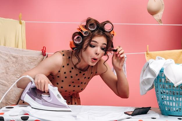 女性、主婦がまな板にアイロンをかけ、同時に化粧をしている。