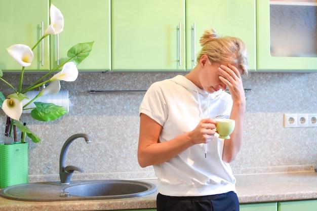 自宅の台所で考えている女性主婦、家庭の問題