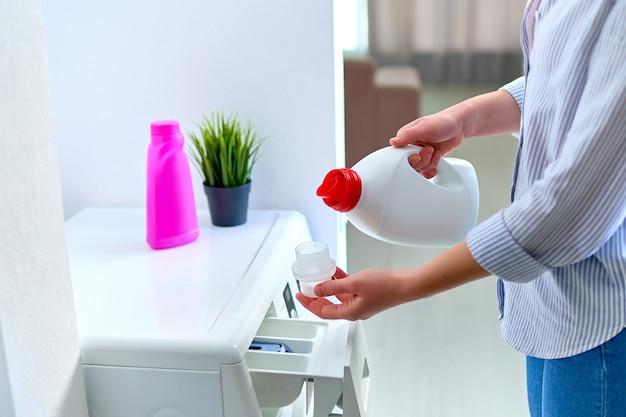 세탁 일에 세탁기에 섬유 유연제 세제 젤을 사용하는 여성 주부