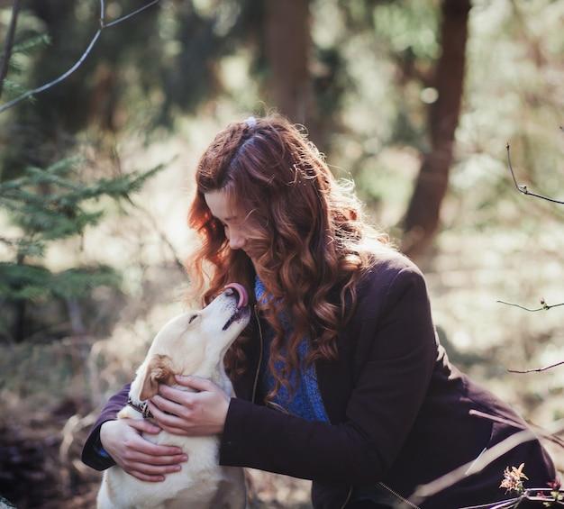 森の中の犬を抱いて女性