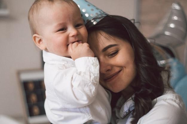 Женщина обнимает и играет со своим маленьким сыном