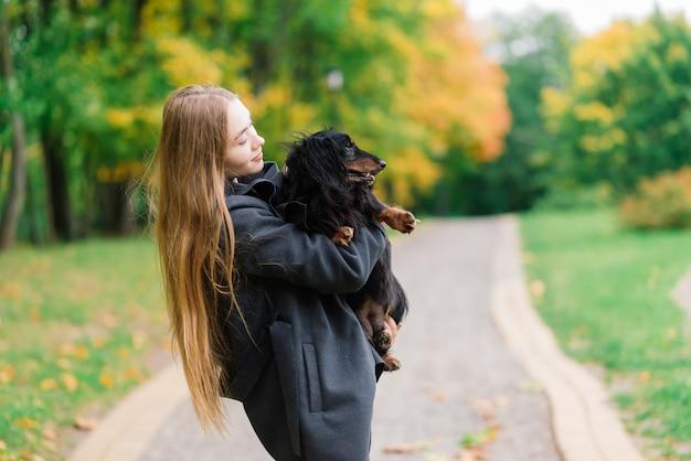 Женщина обнимает собаку в летнем парке. веселая дама с длинными темными волосами обнимает и гладит дружелюбную старую собаку, сидящую на пышном зеленом лугу сквера в хороший день.