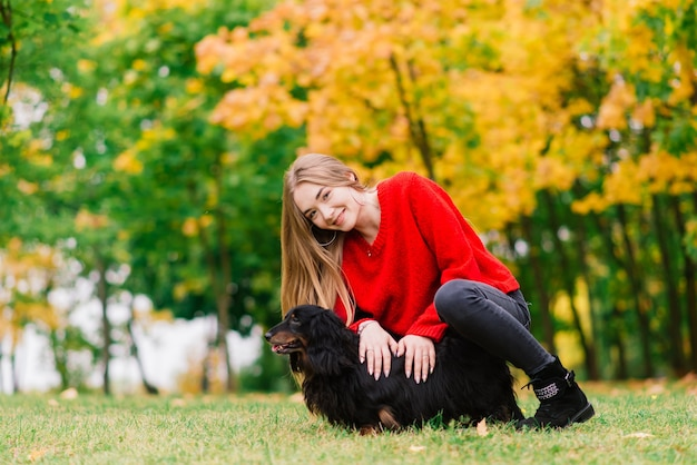 Женщина обнимает собаку в летнем парке
