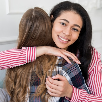 Woman hugging friend and looking at camera