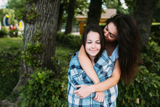 Woman hugging girl wrapped in checkered plaid