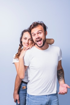 Woman hugging happy man from behind