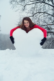 Woman hugging the heart from the snow