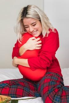 Женщина обнимает подушку на день святого валентина