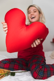 Woman hugging heart pillow on valentines day