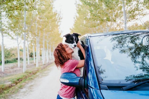 バンで彼女のボーダーコリー犬を抱き締める女性。旅行のコンセプト