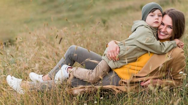 草の中で彼女の男の子を抱き締める女性