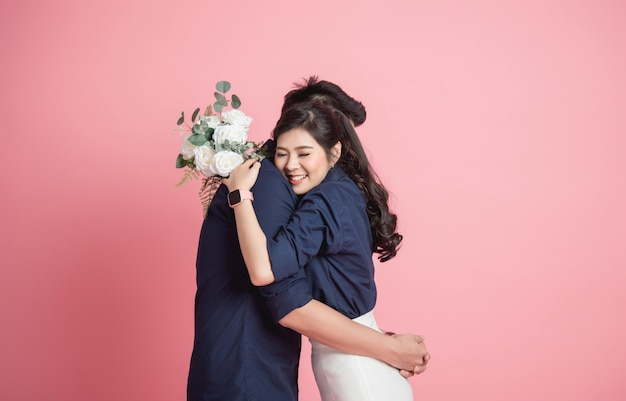 Woman hugging her boyfrienfd with bouquet in hand