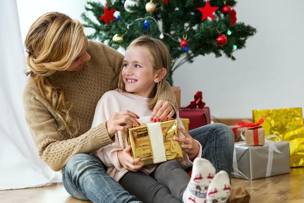 황금 선물 및 선물 배경으로 그녀의 딸을 포옹하는 여자
