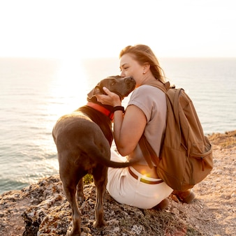 Woman hugging her dog at sunset