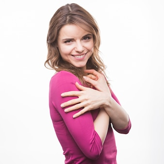 Woman hugging herself on white background