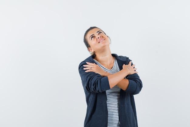Donna che si abbraccia in t-shirt