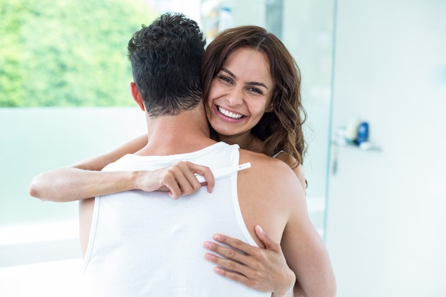 Woman hugging husband while holding pregnancy kit