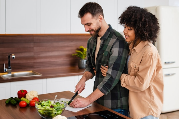 Woman hugging man cooking