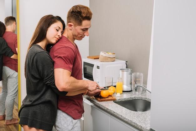 그는 오렌지를 절단하는 동안 남자를 뒤에서 포옹하는 여자