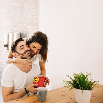 Woman hugging man while giving present