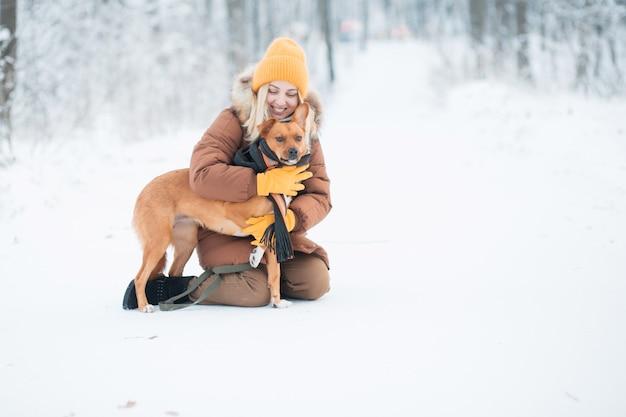 冬の森のスカーフで赤い雑種犬を抱き締める女性。