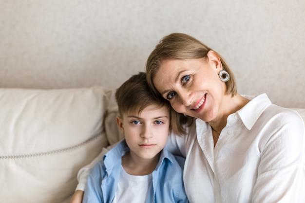 Женщина обнимает подростка и улыбается смотрит в камеру