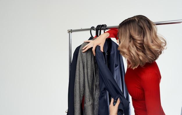 女性は楽屋のショッピングファッションスタイルで服を抱きしめます。