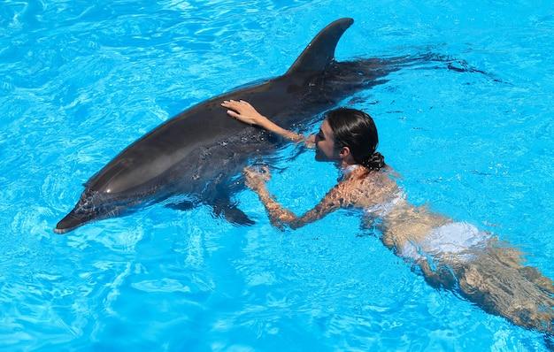 Woman hugs a dolphin in blue water.