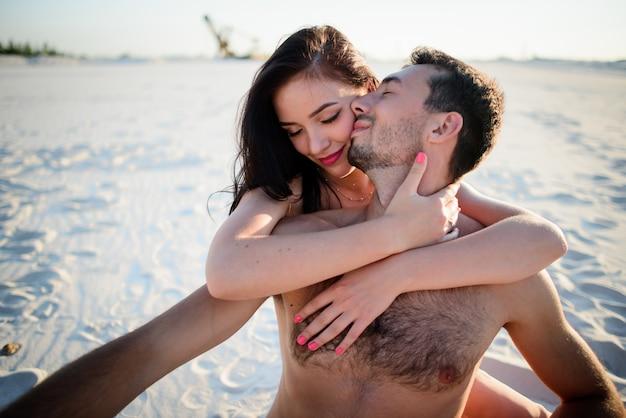 Женщина обнимает мужчину, сидящего на белом песке
