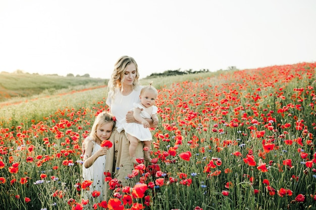 Woman hugs her two daughters among the poppy field