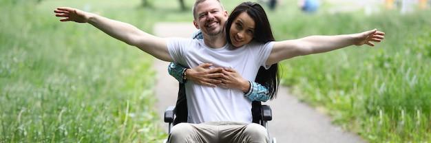 Woman hugs joyful man in wheelchair in park